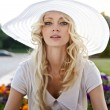 Portrait of beautiful blond woman in white retro hat siting near park — Zdjęcie stockowe