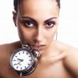 Emotional beautiful mulatto girl holds an alarm clock in a teeth. — Stock Photo #6524460