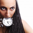 Emotional beautiful mulatto girl holds an alarm clock in a teeth. — Stock Photo #6524470