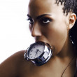 Emotional beautiful mulatto girl holds an alarm clock in a teeth. — Stock Photo