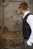 Handsome young man near an old metal door — Stock Photo