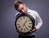 Handsome businessman holding the clock. — Stock Photo