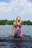 美丽的金发模型站在水。户外概念写真. — 图库照片