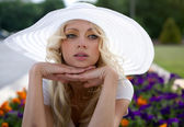 Portrait of beautiful blond woman in white retro hat siting near park — Stock Photo