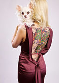 Blond beauty with her little dog and tattoo on her back — Stock Photo