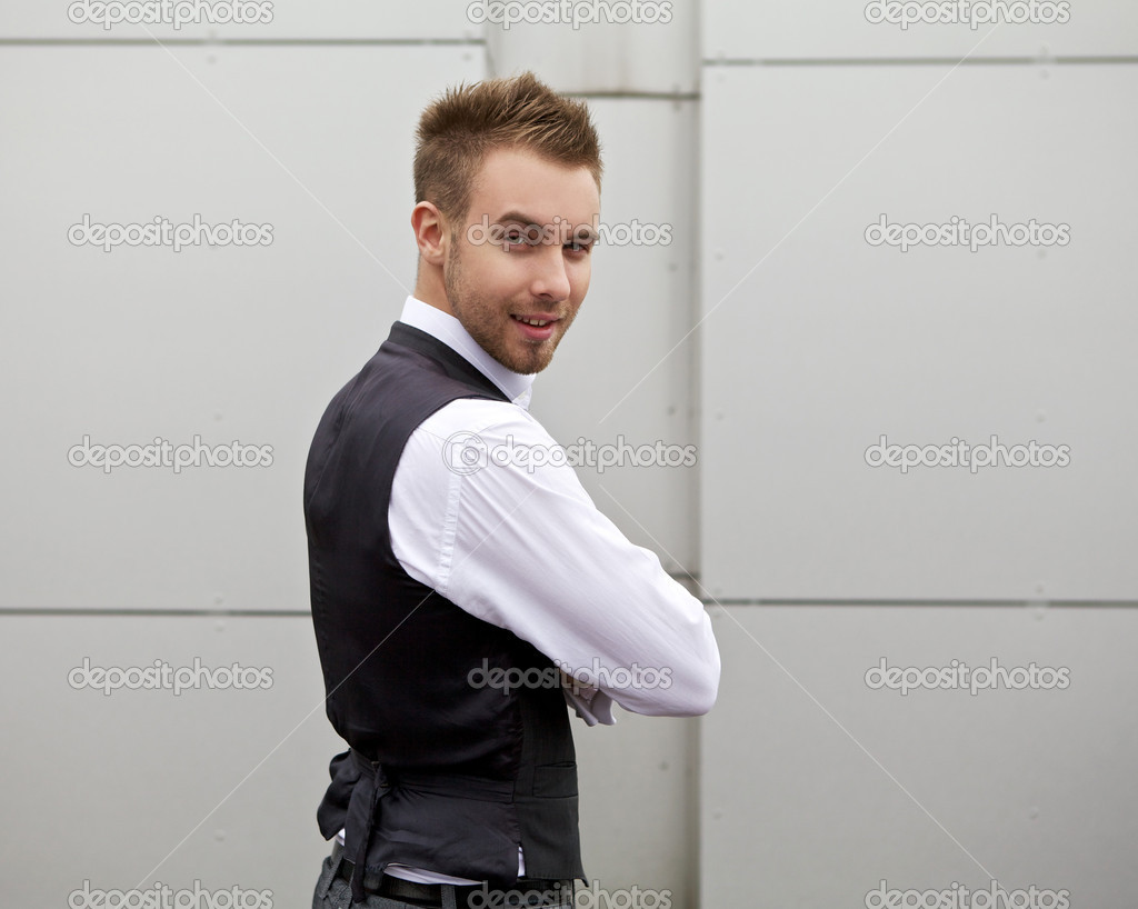 Portrait of a handsome young business man leaning against the metal wall.  Stock Photo #6523511