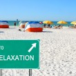 To relaxation sign pointing to beach - Stock Photo