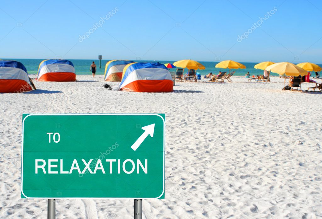 A \' to relaxation \' sign pointing to relaxing on beach chairs under umbrellas in Clearwater Beach, Florida, USA  Stock Photo #5520106
