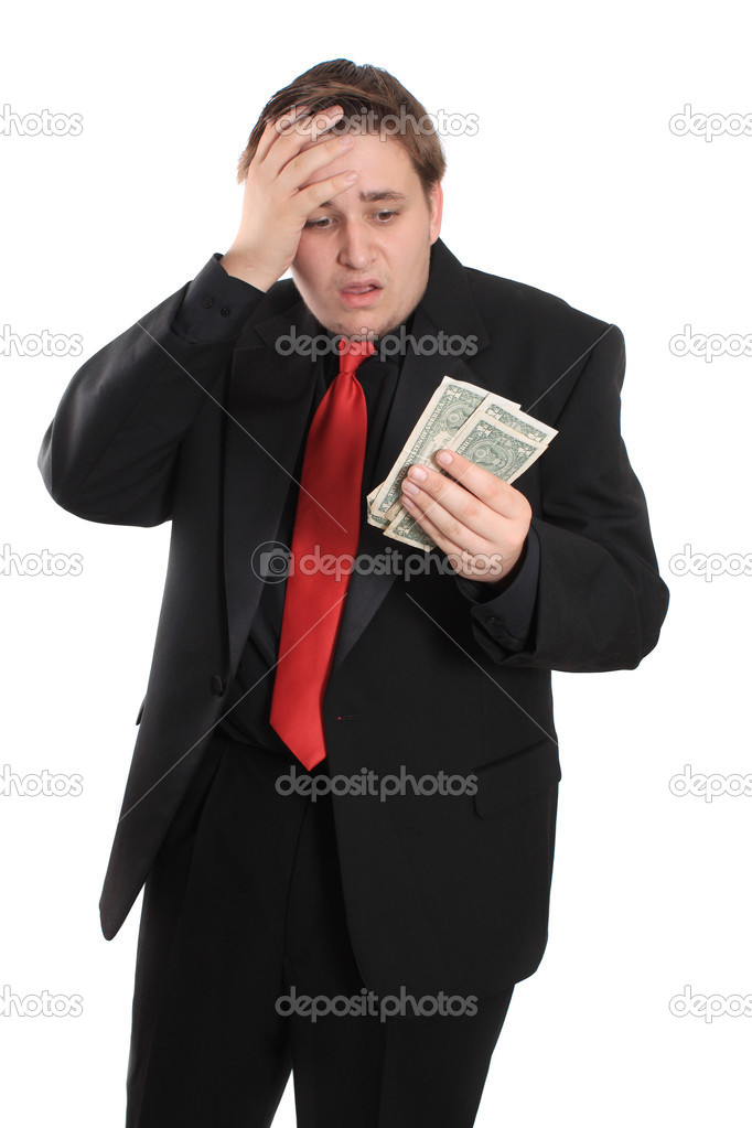 Attractive young man in black suit holding one dollar bills on a white background with shocked expression showing financial loss — Stock Photo #5990930