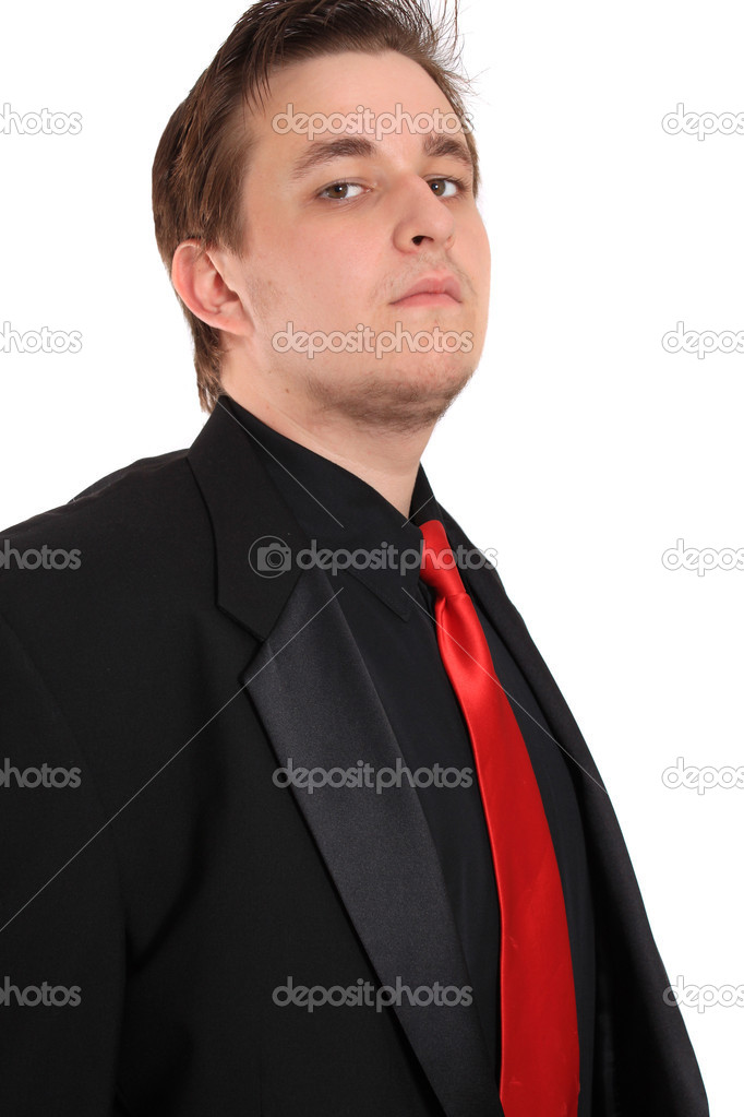 Handsome, cocky young businessman in black formal suit with red tie — Stock Photo #5990938