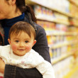 Baby Girl with her Mother in a Shop full of Toys — Stock Photo