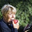 retired woman relaxing outdoor with her smartphone — Stock Photo