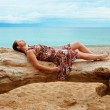 Stock Photo: Womlying on fallen tree on beach
