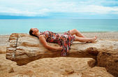 Woman lying on the fallen tree on the beach — Stock Photo