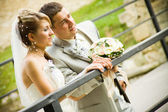 Newly married caucasian couple hugging standing on the bridge — Stock Photo