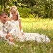 Portrait of happy newlyweds on grass in park — Stock Photo