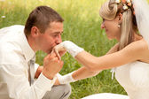 Caucasian prime adult male groom kissing hand of female bride — Stock Photo