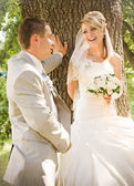 Newly married standing near the tree — Stock Photo