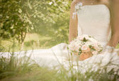 Young beautiful bride with wedding bouquet on the grass — Stock Photo