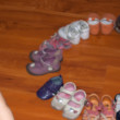 Funny baby girl and her a lot of shoes — Stok fotoğraf