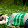Stock Photo: Young pregnant womlaying on grass