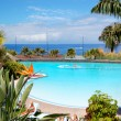 Bird Flower Strelitzia (in focus) and swimming pool and beach of — Stock Photo