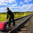 A woman with a suitcase at the railway. — Stock Photo