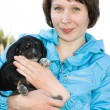 The woman with the puppy in her arms. — Stockfoto