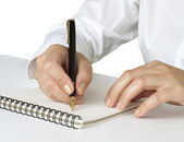 Hand with pen writing on the notebook — Stock Photo