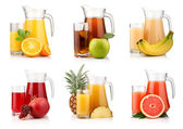 Set of jugs and glasses with tropical fruit juices isolated — Stock Photo