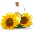 Jug of sunflower oil with flowers isolated — Stock Photo
