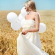 Beautiful girl with white balloons in the field — Stockfoto