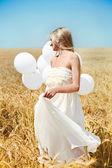 Krásná dívka s bílými balónky v poli — Stock fotografie