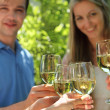 Celebration. holding glasses of white wine making a toast — Stock Photo