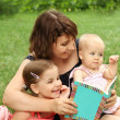 Mother and children reading a book i — Stock Photo