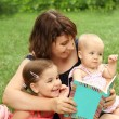 Mother and children reading a book i - Stock Photo