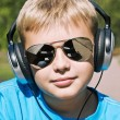 Boy listening to music through headphones - Stock Photo
