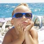 The boy in a sun glasses sunbathes on a beach — Stock Photo
