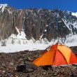 Orange tent in high mountains - Stock Photo