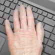Hand in rubber glove resting on laptop keyboard - Foto Stock