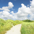 Clouds over unsealed sandy road between dunes — Stock Photo