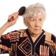 The elderly woman brushes hair - Stock Photo