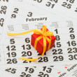 Box with a gift on calendar sheet - Valentines day - Stock Photo