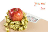 Scale, tape and apple on white background — Stock Photo