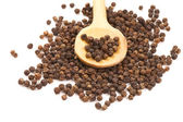 Black Peppercorns on a wooden spoon — Stock Photo