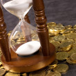 Hourglasses and coin On a grey — Stockfoto