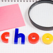 Magnifier on a school writing-book - Stock Photo