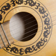 Close-up old acoustic guitar as background - Stock Photo