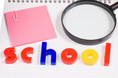 Magnifier on a school writing-book — Stock Photo