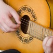 The man plays an acoustic guitar - Stock Photo